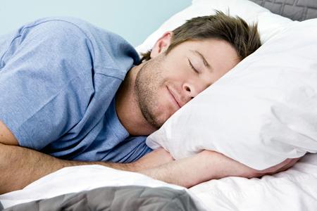 Hübscher Mann liegt schlafend im Bett und schmunzelt, weil er im Schlaf abnehmen kann.