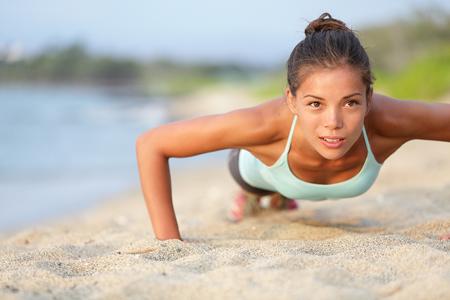 Hübsche Frau macht Liegestütze am Strand, um Bauch Beine Po zu trainieren.