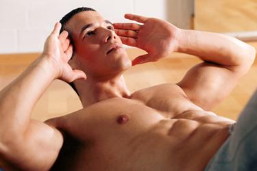Durchtrainierter Mann, der Bauchübungen macht.