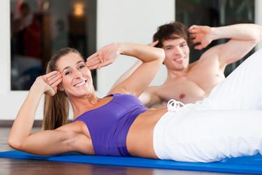Fröhliche Frau und fröhlicher Mann, die auf dem Rücken ihr Sixpack Training machen.