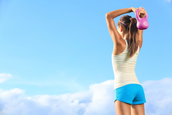Schöner blauer Himmel mit einigen Wolken und einer sportlichen Frau die eine Kettlebell in den Händen hält.