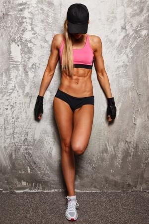 Frau zeigt flachen Bauch in sportlichem Look und an der Wand gelehnt.